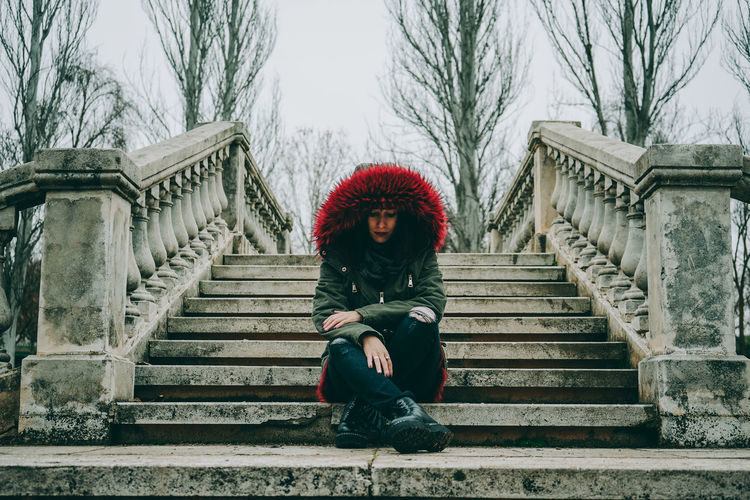 Full length portrait of woman sitting on staircase