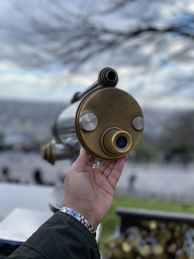 Close-up of hand holding metal scope against sky