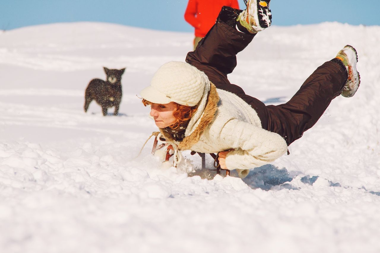 Young woman sledding on snow covered field during winter