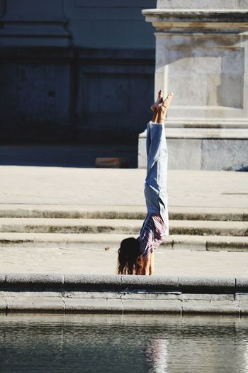 Woman doing handstand by pond