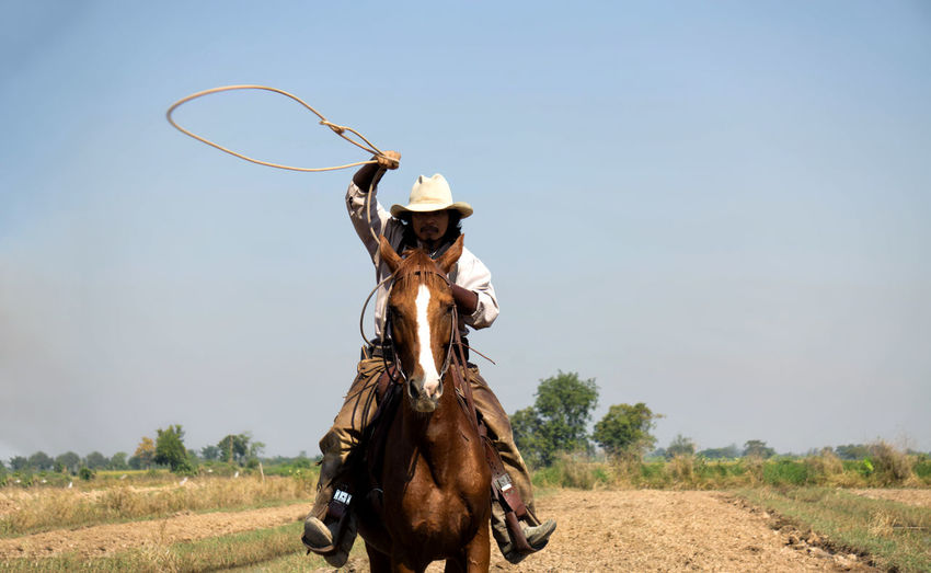Man holding noose while riding on horse against sky