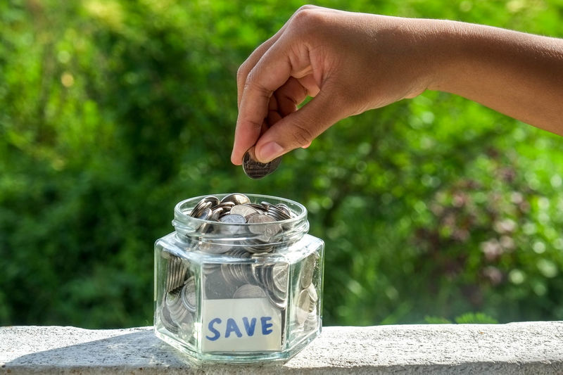 Close-Up Of Human Hand Holding Coins Over Jar With Save Label On Retaining Wall