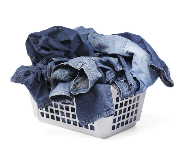 A Laundy basket filled with only jeans. Isolated on white with natural shadows.