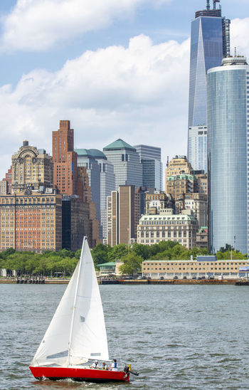 Sailboat in river by buildings against sky