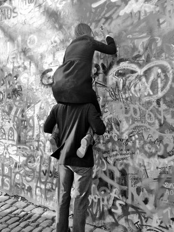 Love while overwritten is never totally lost. Boost Casual Clothing Couple Day Exploration Footpath Graffiti Love Monochrome Monochrome Photography Person Piggyback Standing The Past Three Quarter Length