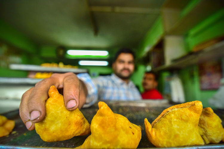 "The Street Photographer - 2017 EyeEm Awards indian sweetshop's scene , Shopkeeper picking up a dish called ""samosa"" , to give it to customer Indiapictures Indian Food Foodstagram Food Foodporn Indian Street Photography Streetphotography"