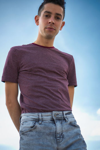 Portrait of young man standing against sky