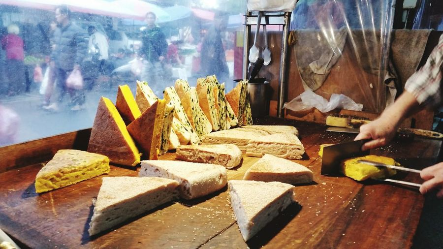 Cropped image of vendor cutting food at market stall