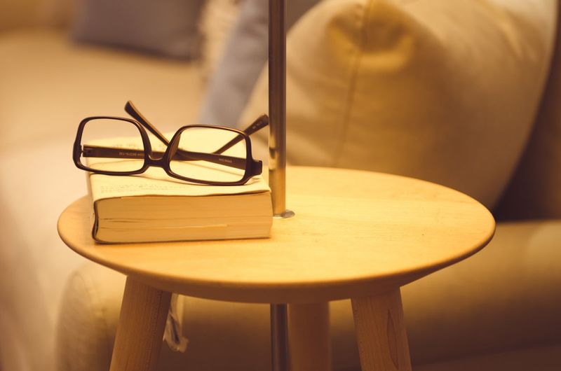 Close-up of eyeglasses and book on table