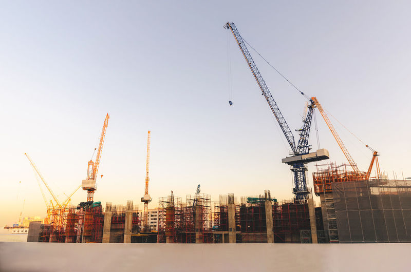 Cranes at construction site in city against clear sky