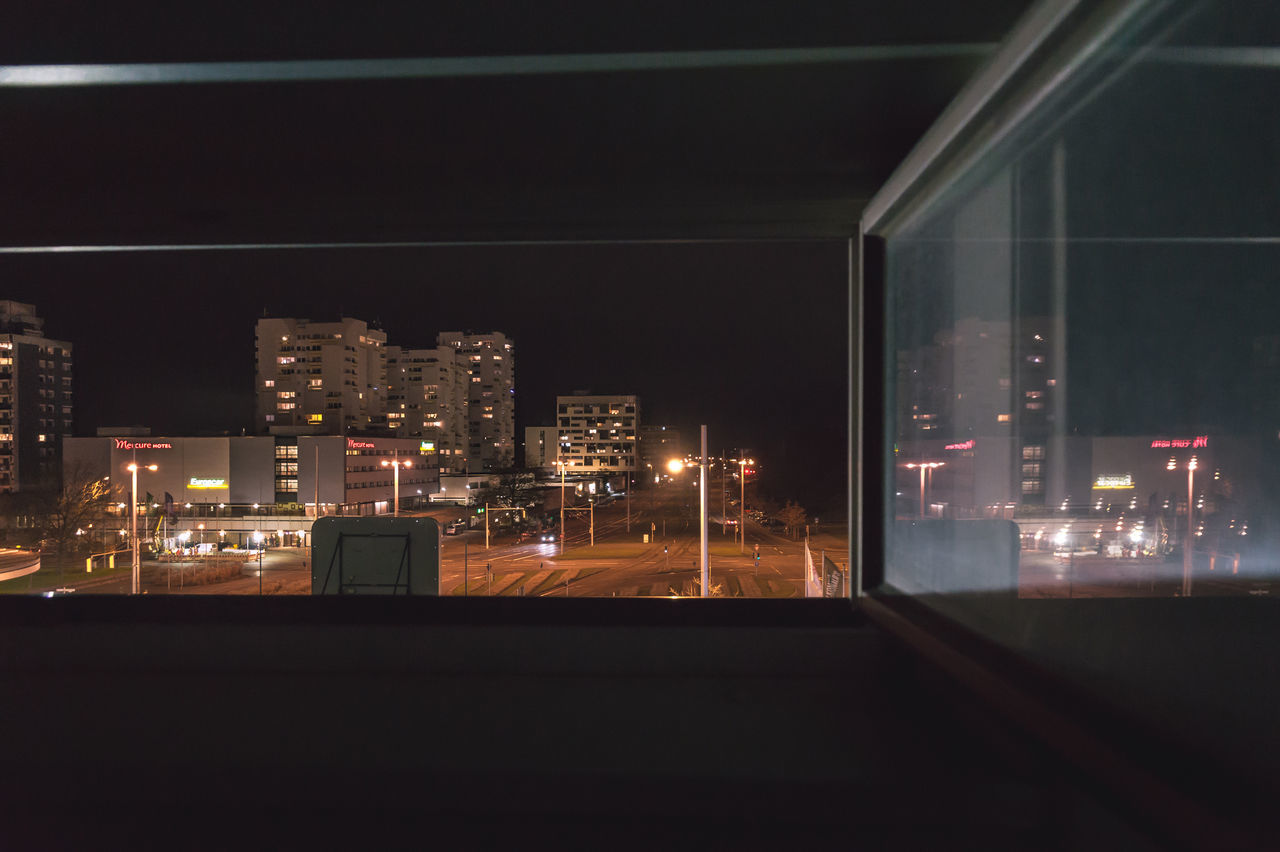 Buildings Against Sky In City Seen Through Window At Night