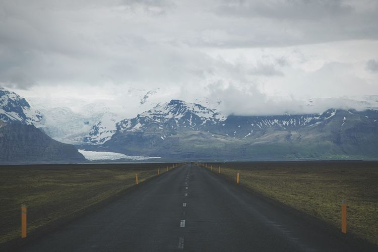 Road passing through snow covered mountains against cloudy sky