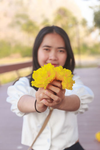 Portrait of woman holding yellow while standing outdoors