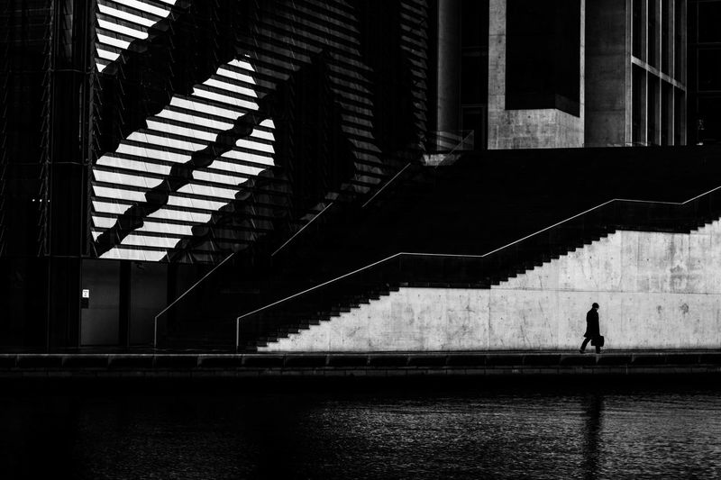 Silhouette man walking by staircase against building