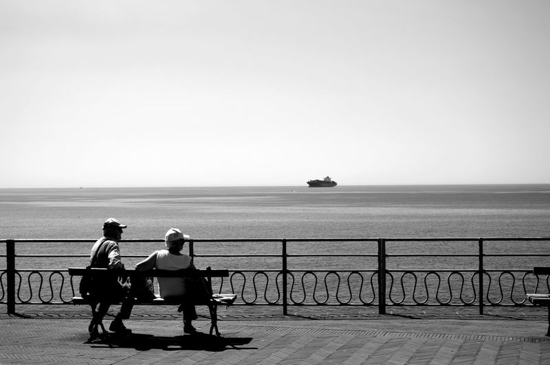 Rear view of man and woman sitting on bench at promenade by sea against clear sky
