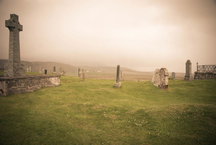 Tranquil Scene Of Cemetery Against Sky During Foggy Weather