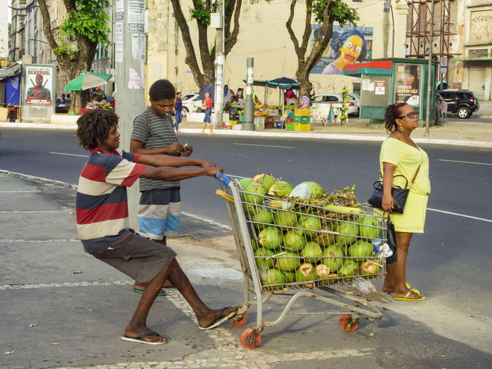 young colored brazilian man pushing a shopping venture full of coconuts across the street Coconut Crossing The Street Basket With Coconuts Brazilian Streetlive Food Heavy Load Outdoors Real People Selling Food Shopping Venture
