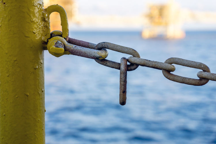 Close-up of chain on railing against sea