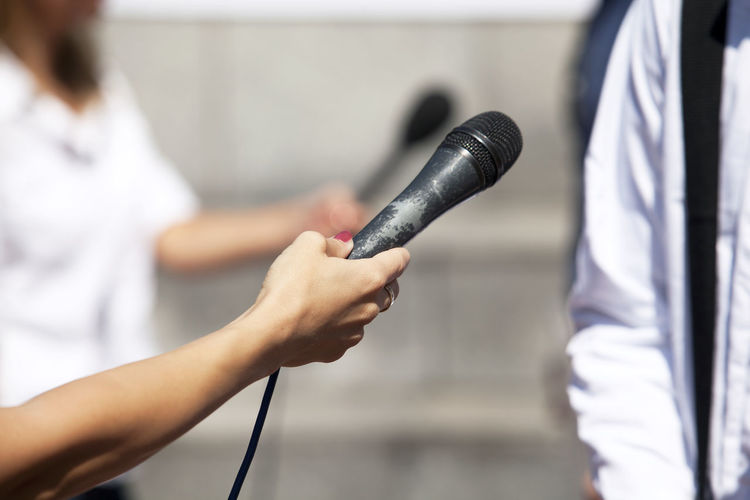 Cropped Hand Of Journalist Holding Microphone For Man