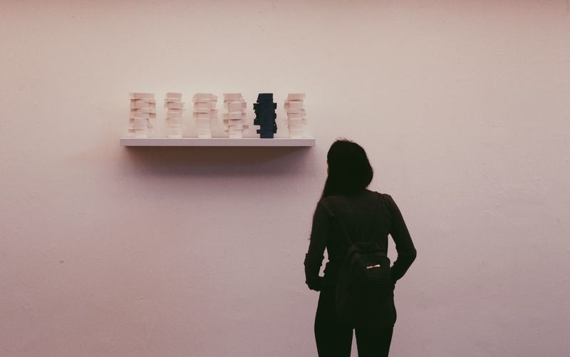 Rear view of silhouette woman standing against wall