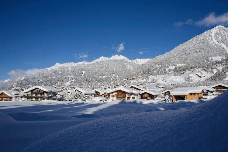 Houses on snowcapped mountain against blue sky
