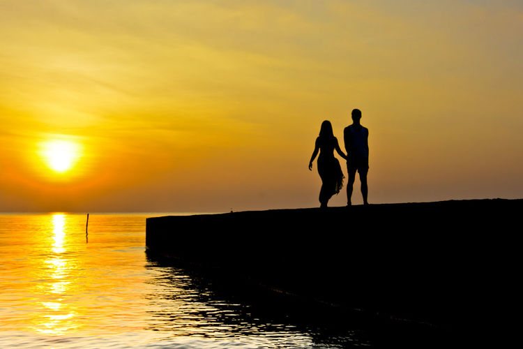 Sunset at beach Adult Adults Only Beauty In Nature Bonding Friendship Full Length Honeymoon Lake Leisure Activity Lifestyles Love Story Loving Men Nature Outdoors People Real People Reflection Silhouette Sky Sun Sunlight Sunset Togetherness Weekend Activities