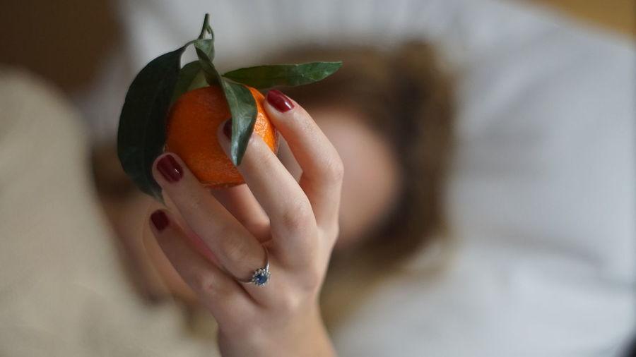 Close-up of woman holding orange fruit