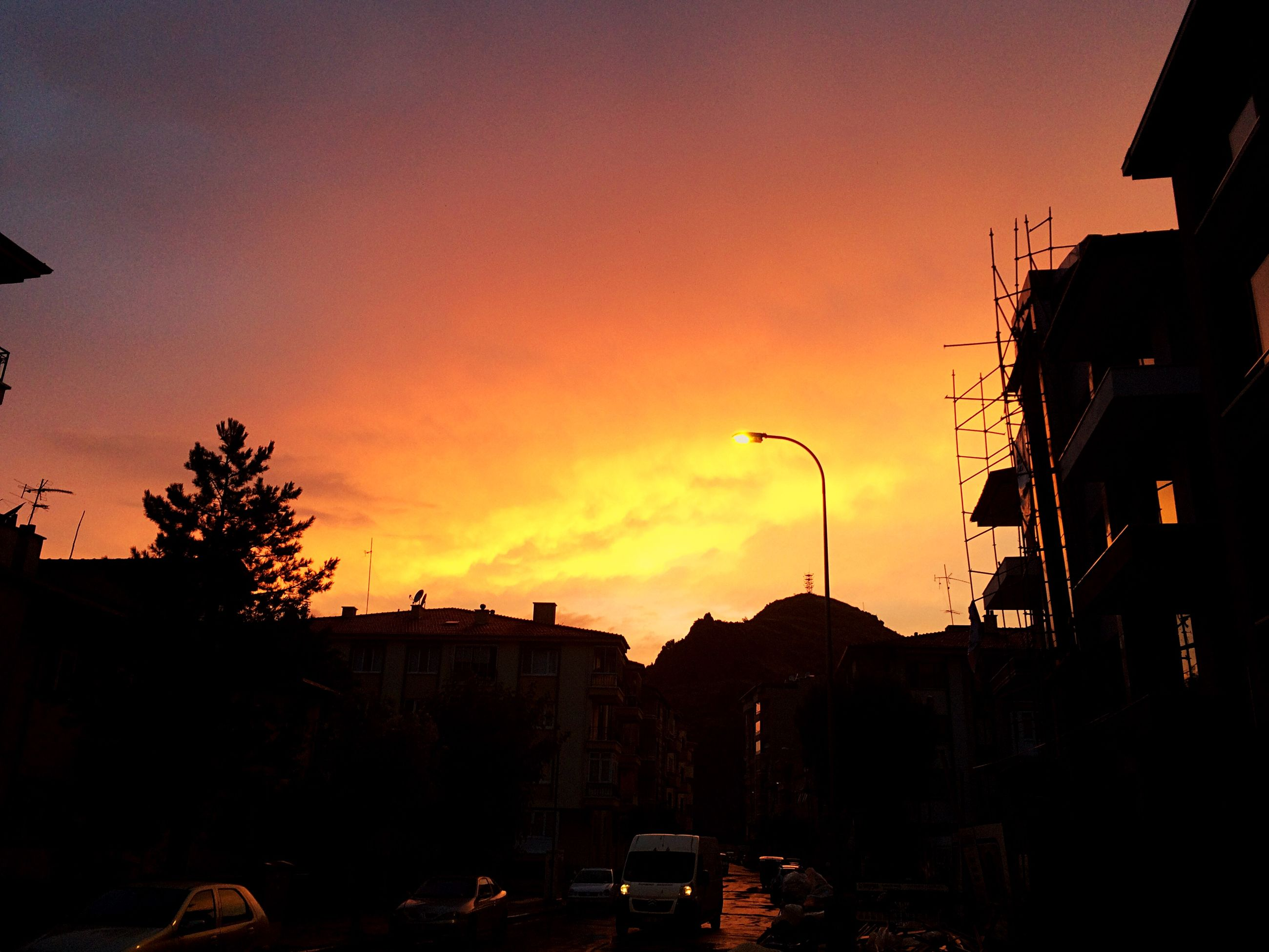 sunset, building exterior, architecture, built structure, silhouette, car, sky, city, land vehicle, orange color, transportation, street light, street, tree, residential structure, dusk, house, mode of transport, residential building, building