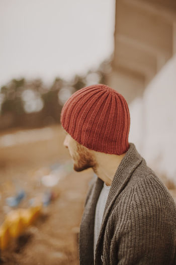 Side view of young man wearing knit hat standing against sky