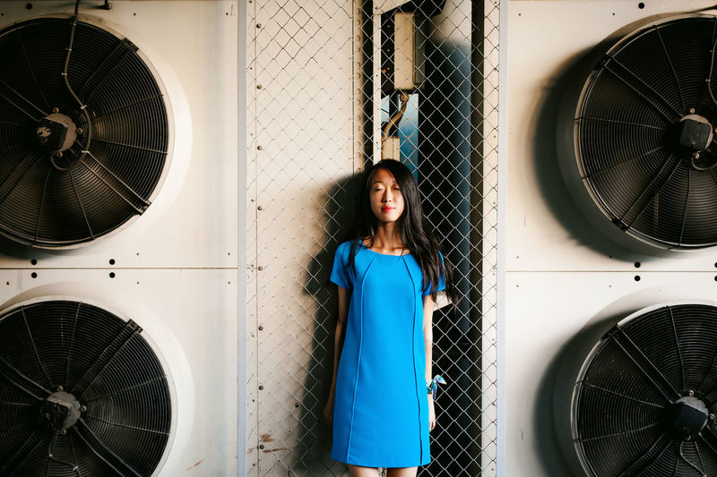 Young woman standing amidst exhaust fans