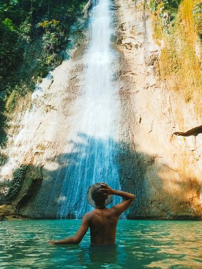 Rear view of shirtless man in watter fall