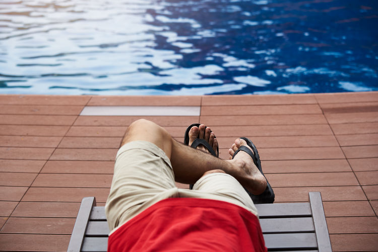Low section of man relaxing on chair by swimming pool