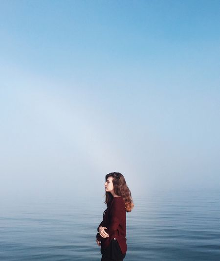 Side view of woman standing by sea against clear sky