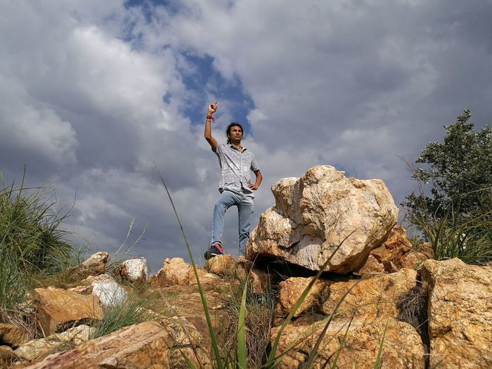 Low Angle View Of Man Gesturing While Standing On Rocks Against Cloudy Sky