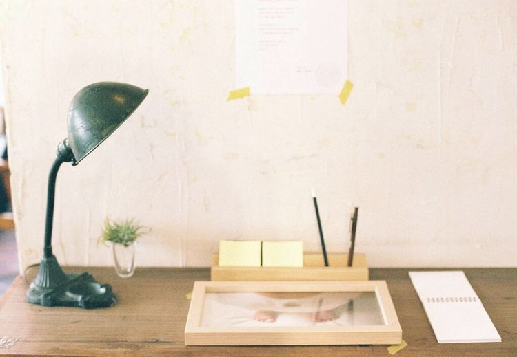 Desk Lamp On Wooden Table By Wall At Home