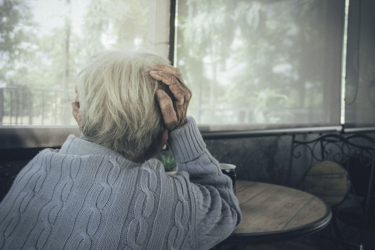 Rear view of old woman sitting by window at home. concept loneliness, dementia, abuse, sadness.