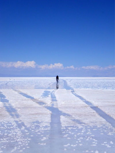 Man on riding bicycle on salt flat at salar de uyuni