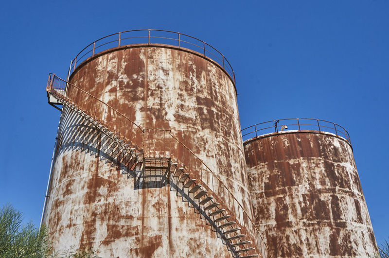 Low angle view of old rusty silos against clear sky