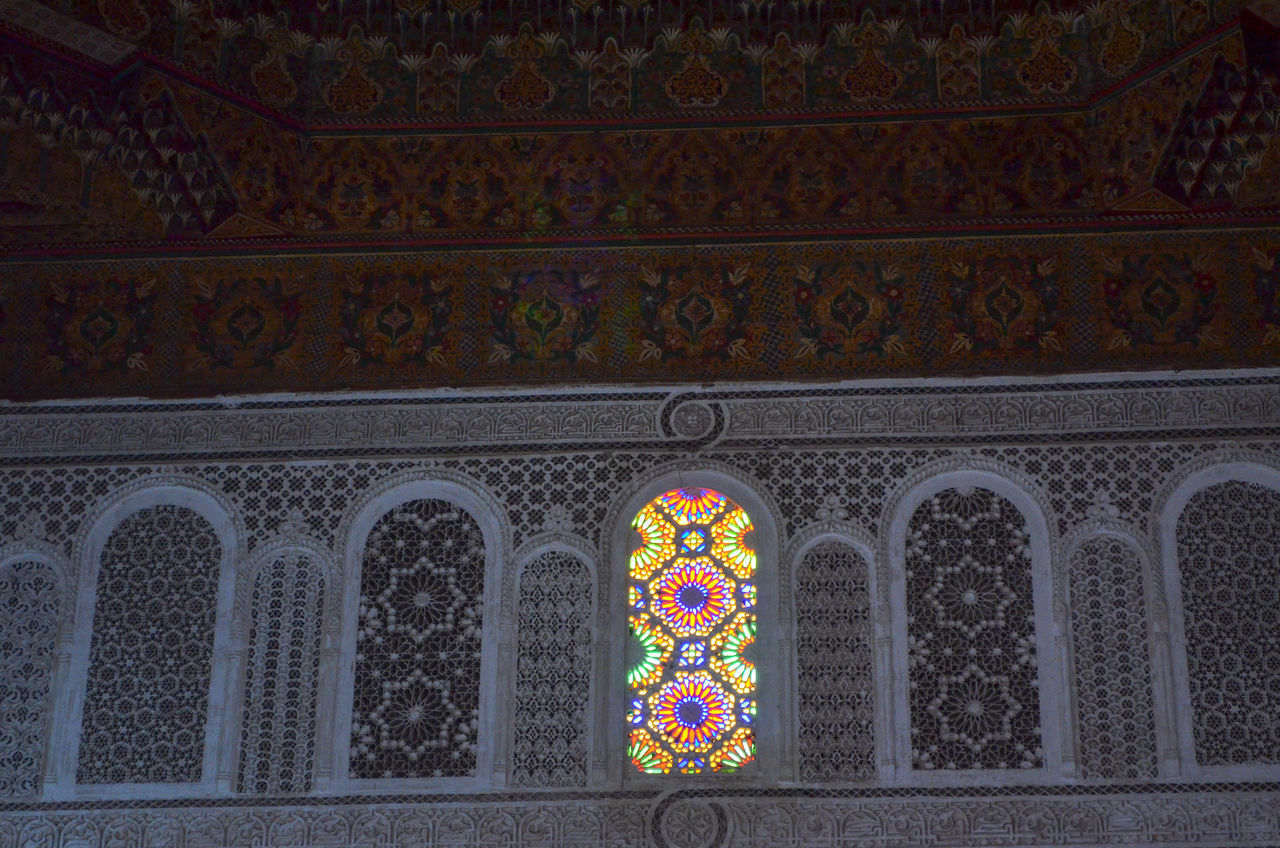 LOW ANGLE VIEW OF CROSS ON PATTERNED WALL