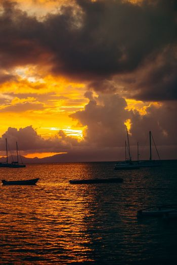 Silhouette of sailboat in sea during sunset