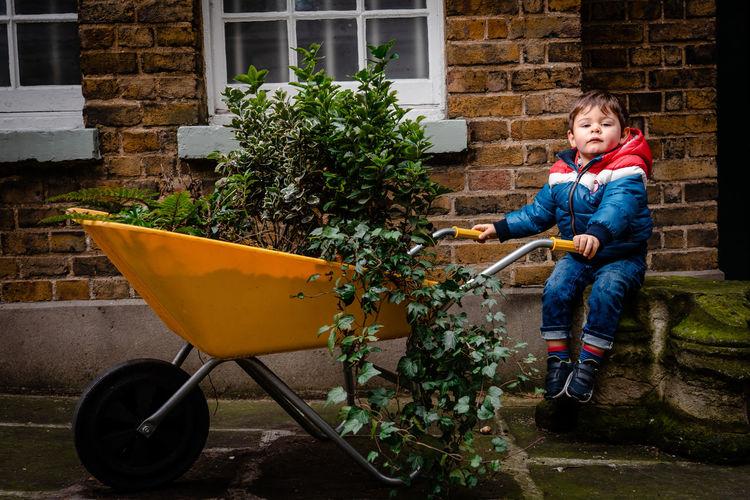 Portrait of boy holding umbrella in yard