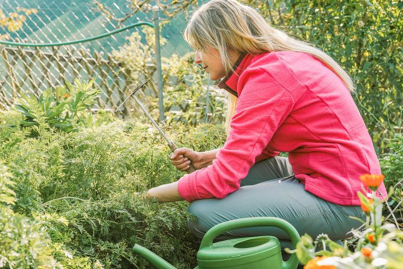 Side View Of Woman Gardening In Yard