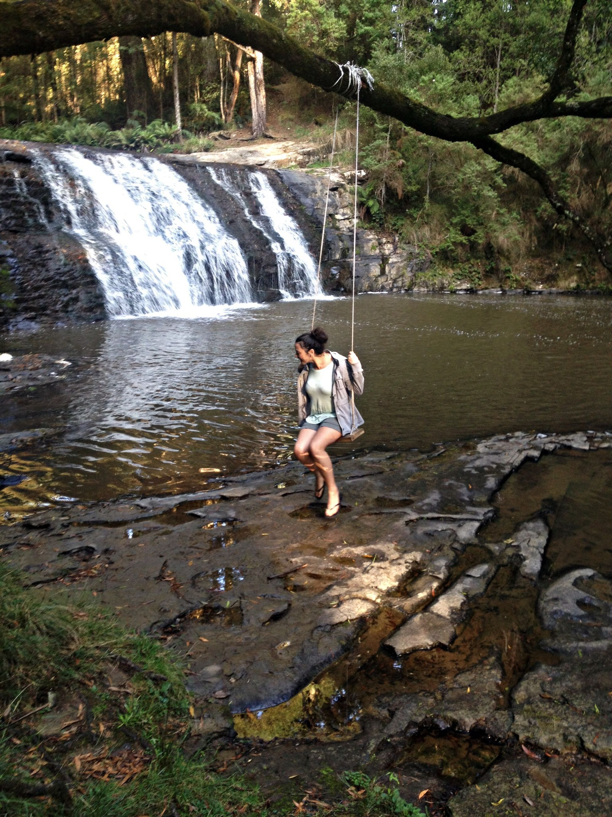 water, full length, lifestyles, leisure activity, casual clothing, rock - object, standing, motion, person, young adult, nature, rear view, river, forest, day, flowing water, elementary age, waterfall