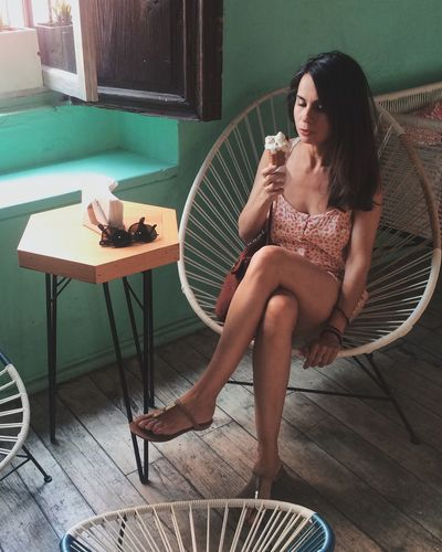 Woman eating ice cream while sitting on chair