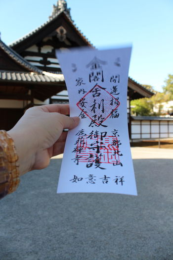 A unique ticket for Kinkakuji (金閣寺, Golden Pavilion) at Kyoto, Japan Adult Calligraphy Chinese Words Close-up Day Handwriting  Holding Human Body Part Human Hand Japanese Culture Kikakuji Kyoto, Japan Outdoors Paper People Sky Sky And Clouds Sunny Day Text Ticket