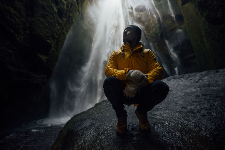 Full length of man crouching against waterfall in cave