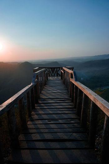 Empty long wooden footbridge against clear sky