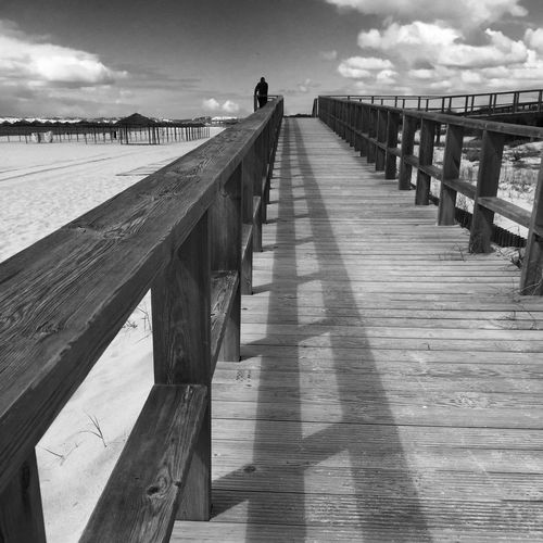Wooden pier on river against cloudy sky