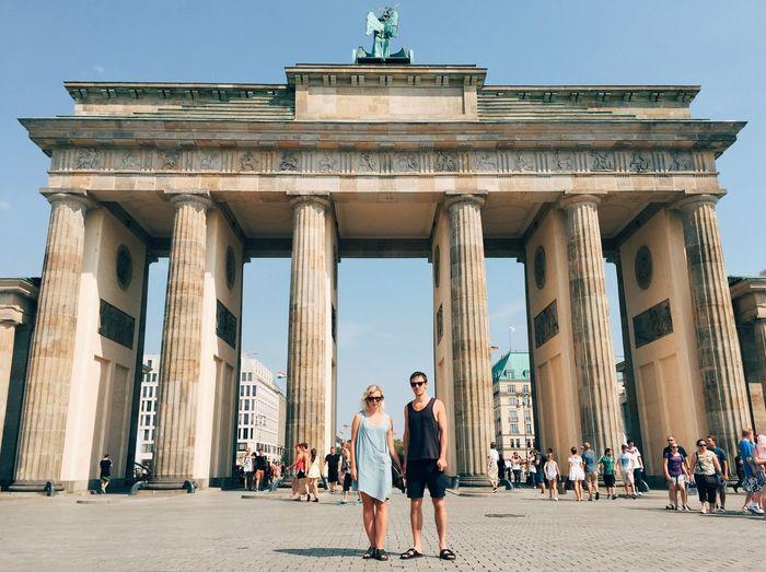 Portrait of friend standing against brandenburg gate