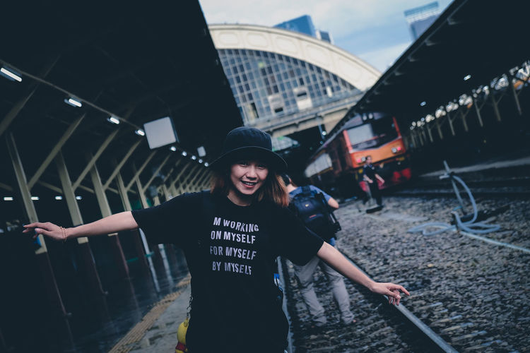 Portrait of smiling young woman with arms outstretched standing on railroad station platform